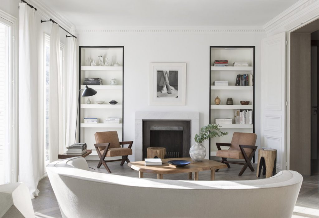 Jeanneret easy chairs flank the fireplace in this Paris apartment by Nicolas Schuybroek