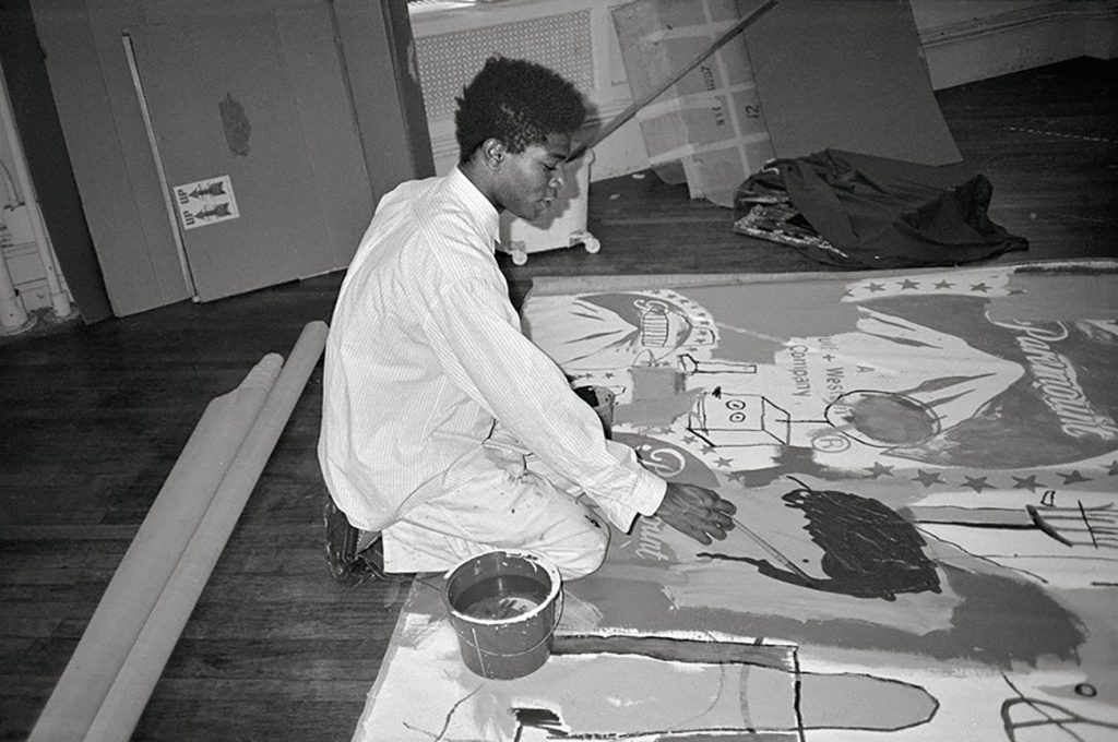 Jean-Michel Basquiat at work in Andy Warhol's studio in 1984