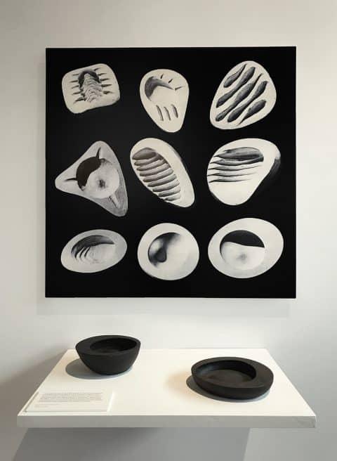 An image of plaster Noguchi ashtray prototypes, c. 1944, hangs above iron Bonniers bowls/ashtrays at the exhibit
