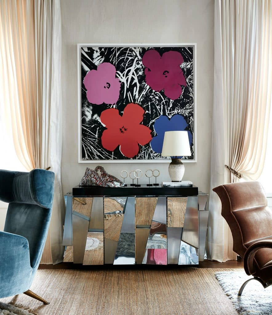 Andy Warhol flower painting hangs above a Paul Evans cabinet in the living room of a Manhattan duplex by Robert Stilin