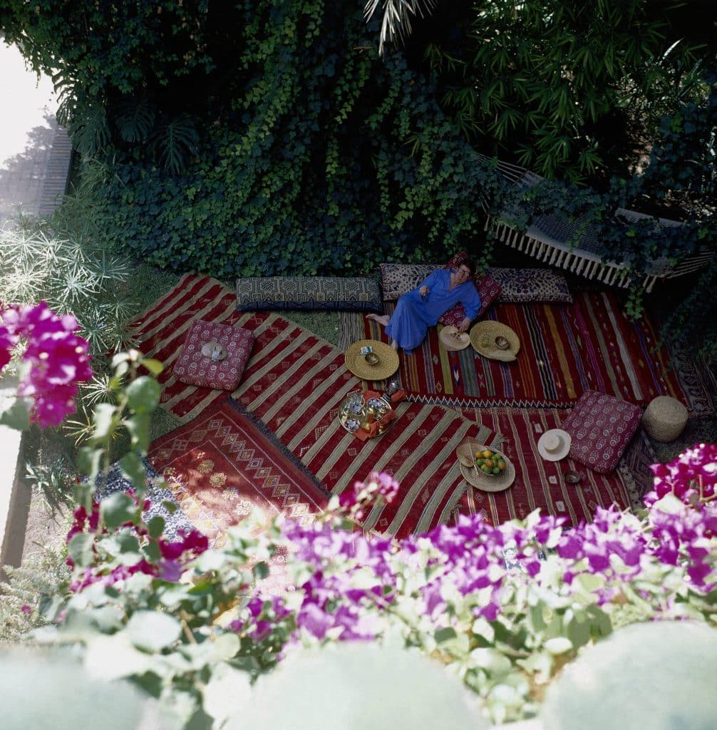 Overhead shot of Saint Laurent reclining in his leafy Moroccan garden, strewn with rugs and pillows, wearing a blue caftan. Photo by Horst P. Horst/Condé Nast via Getty Images