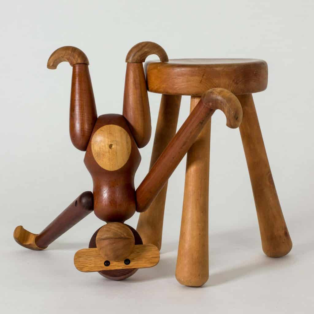 Kay Bojesen teak monkey toy, 1950s, hanging from a stool