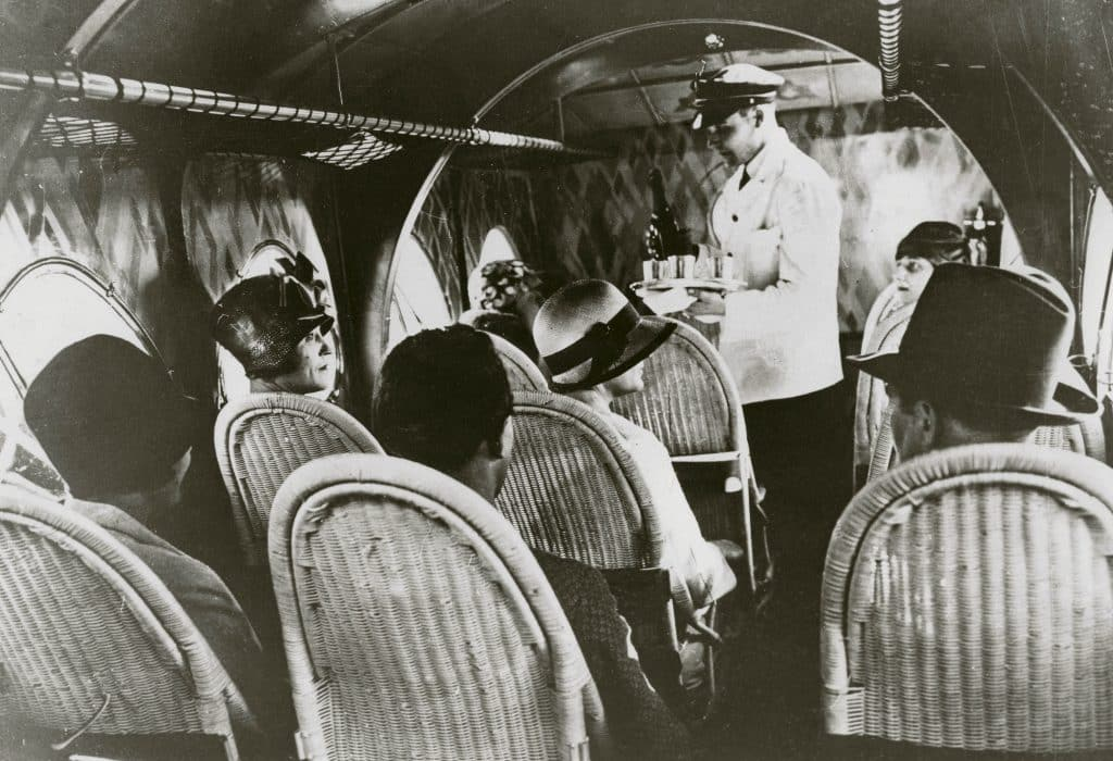 In a black-and-white photo from the book Rattan: A World of Elegance and Charm, by Lulu Lytle, published by Rizzoli, passengers sit in rattan seats on an airline flight circa 1930.