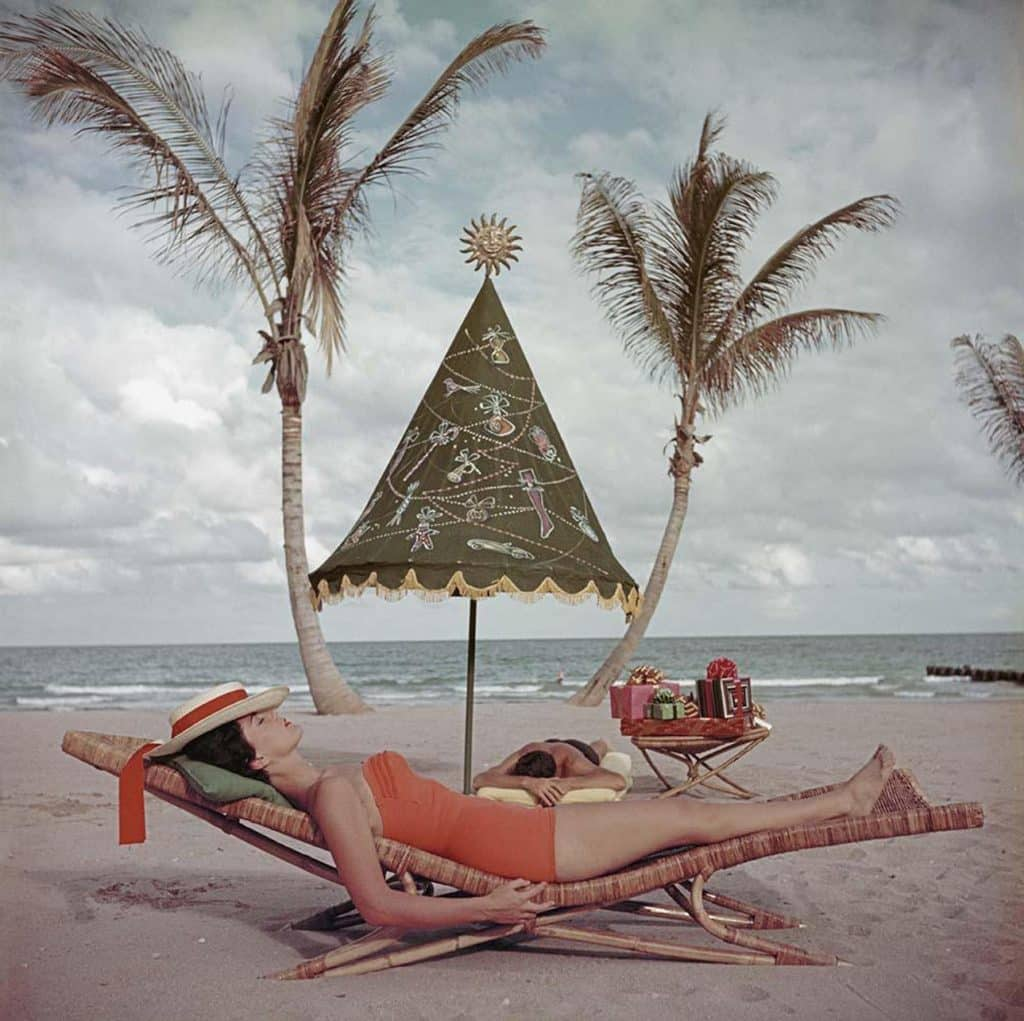 A woman relaxes on a rattan chaise in Palm Beach, as seen on the cover of Holiday magazine in December 1955 and now in the book Rattan: A World of Elegance and Charm, by Lulu Lytle, published by Rizzoli