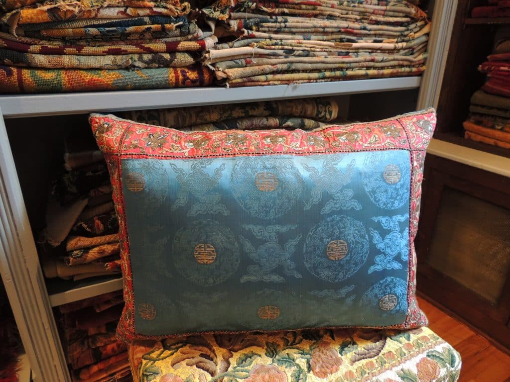 A pillow made from an antique blue-and-gold silk Japanese obi, created by Antique Textiles Galleries