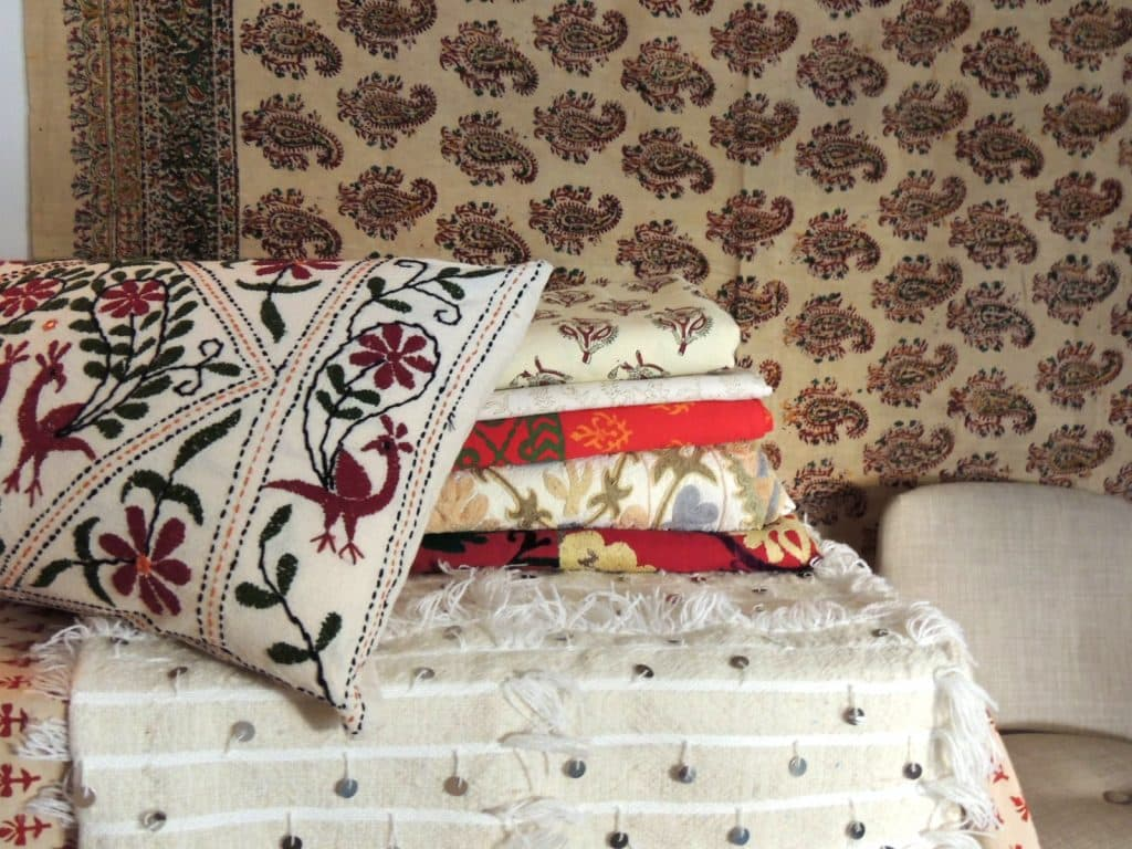 A vintage hand-blocked red and brown Kalamkari cotton paisley coverlet/cloth hangs in the background. On the table is a stack of vintage hand-blocked Indian bed covers and vintage embroidered suzanis from Uzbekistan, and a pillow made from vintage Indian colorful floral embroidered fabric, laying on top of a Moroccan beige and white wedding blanket with white fringe and silver sequins. All available from Antique Textiles Galleries.