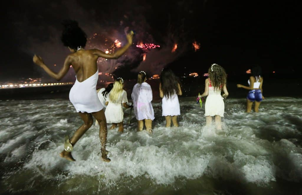 Revelers jumping waves in Brazil at midnight, a New Year's tradition meant to bring good luck in the year ahead.