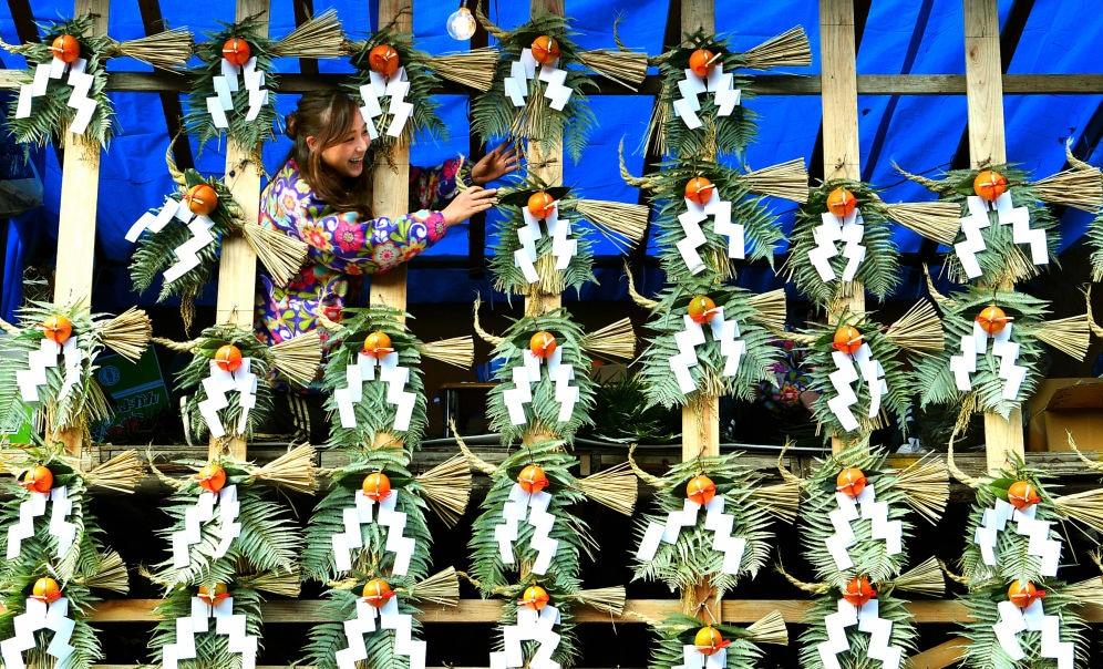 A vendor selling shimekazari New Year's ornaments, which are meant to bring good fortune, outside the Kiyoshikojin Seichoji Temple in Takarazuka, Japan.