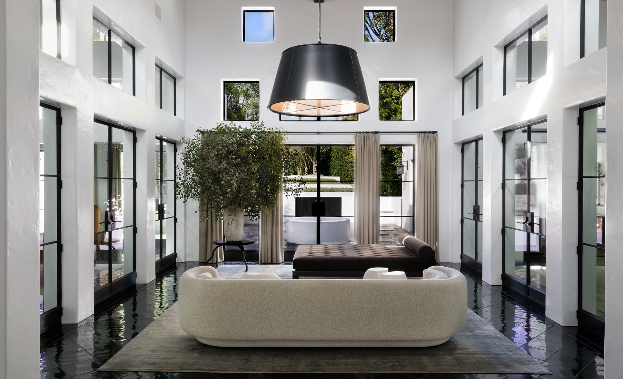 Steel casement windows and doors, bare white walls, black floors, and lamps with black oversize shades in Ryan Murphy's home in Pacific Palisades, designed by Stephen Shadley