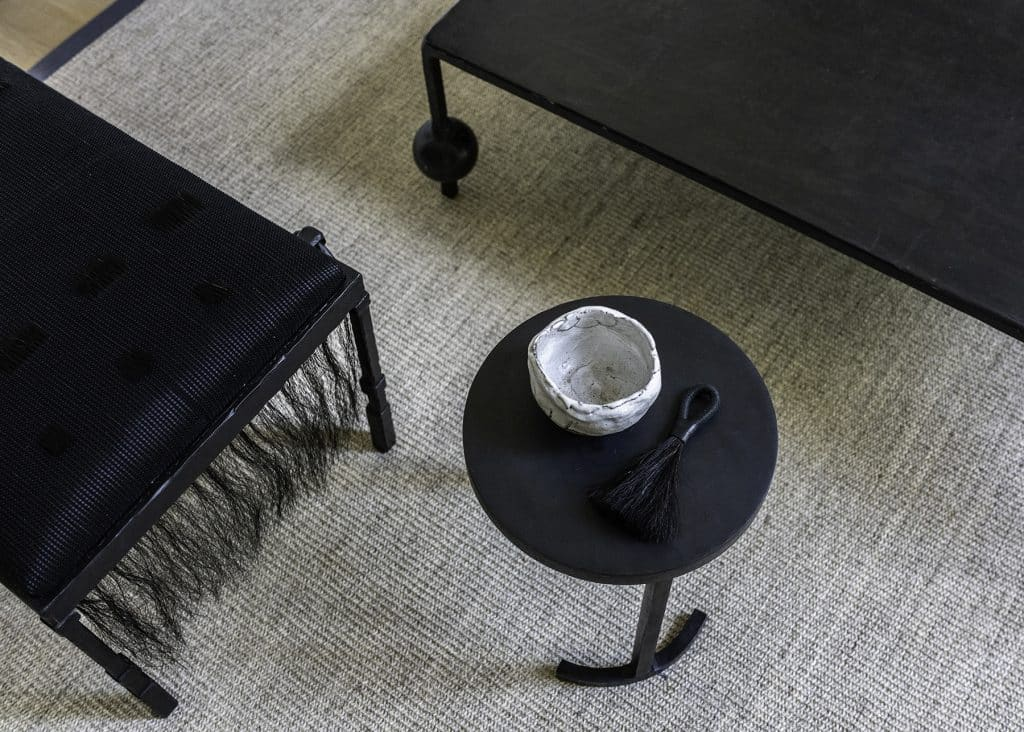 A horsehair and iron bench, blackened-steel cocktail table and two-legged side table.