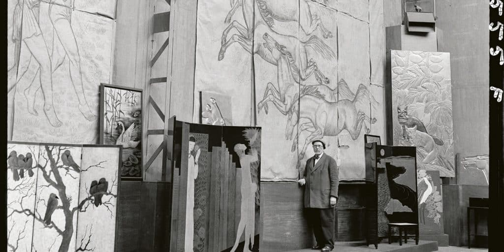 Jean Dunand poses amid an array of his panels and screen