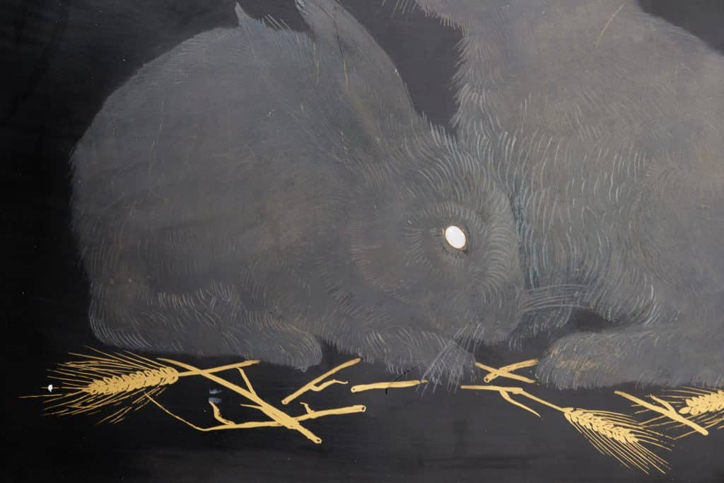 A detail of a ca. 1926 panel by Jean Dunand depicting a pair of rabbits with opals for eyes, offered by Maison Gerard