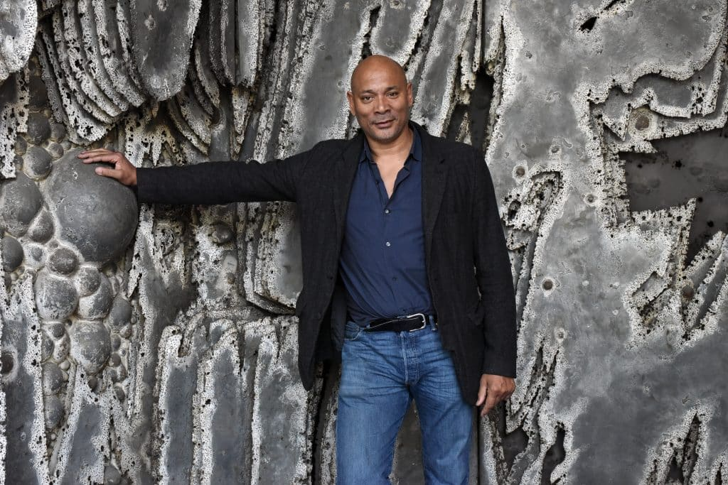Hugues Magen, owner of Magen H Gallery, poses with a large-scale work by artist Pierre Sabatier
