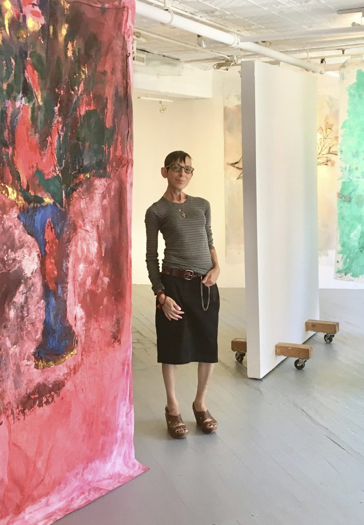 Ivy Brown poses among paintings by Joel Handorff in her eponymous Manhattan art space