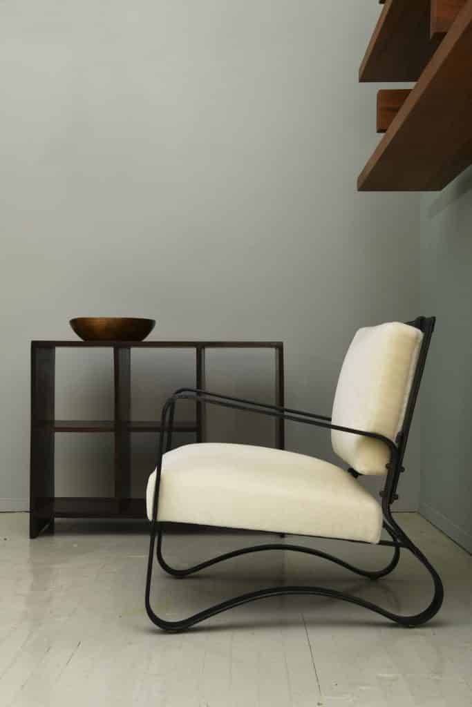 A Jacques Adnet leather chair sits next to a Pierre Jeanneret shelf at Magen H Gallery
