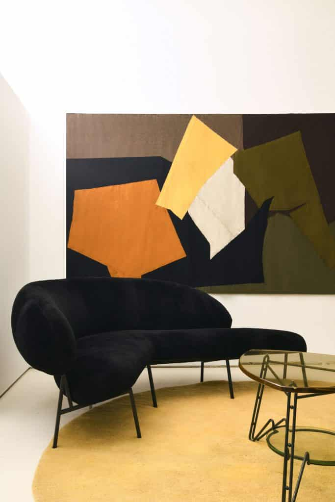A Michael Bargo–designed room at Magen H Gallery in New York, featuring Pierre Székely's 1953 Boomerang sofa, a 1970 wool tapestry by artist Claude Stahly and a glass Italian side table