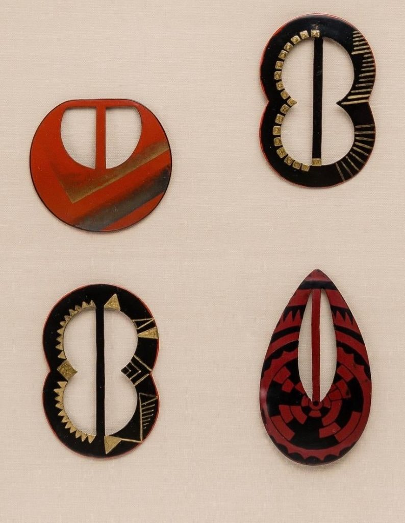 Four lacquer belt buckles designed by Jean Dunand, offered by Galerie Marcilhac