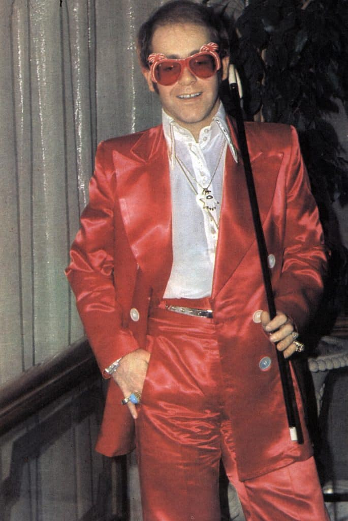 Elton John sports a pair of his trademark sunglasses and Aldo Cipullo's Hand of the Heart necklace in 1973.