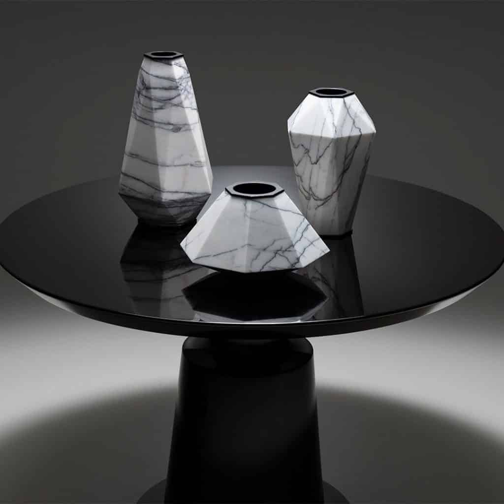 Large, medium and small marble and steel Warrior vases, created for Holly Hunt by jewelry designer Eva Fehren, resting on the Holly Hunt Peso side table