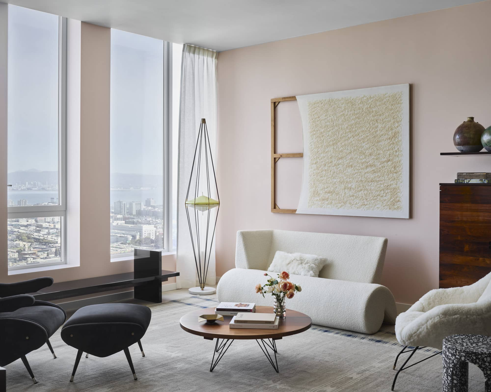 A white Martin Szekely sofa and an Acácio Gil Borsoi jacaranda coffee table in the living room of Gabriel & Guillaume's staged apartment at Fifteen Fifty in San Francisco