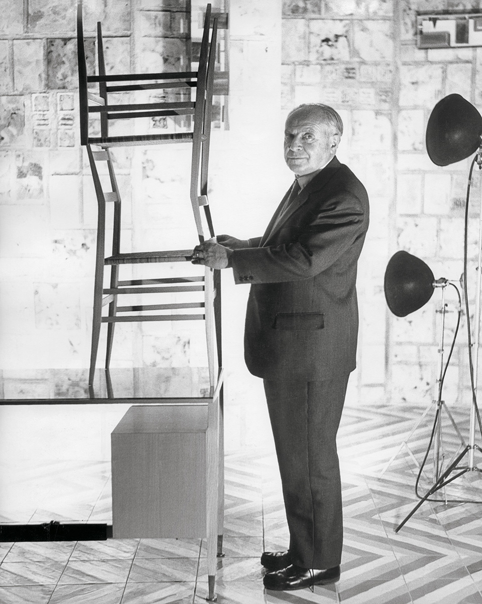 Gio Ponti posing for a 1959 portrait with his Superleggera chairs, from the book Gio Ponti, offered by Taschen