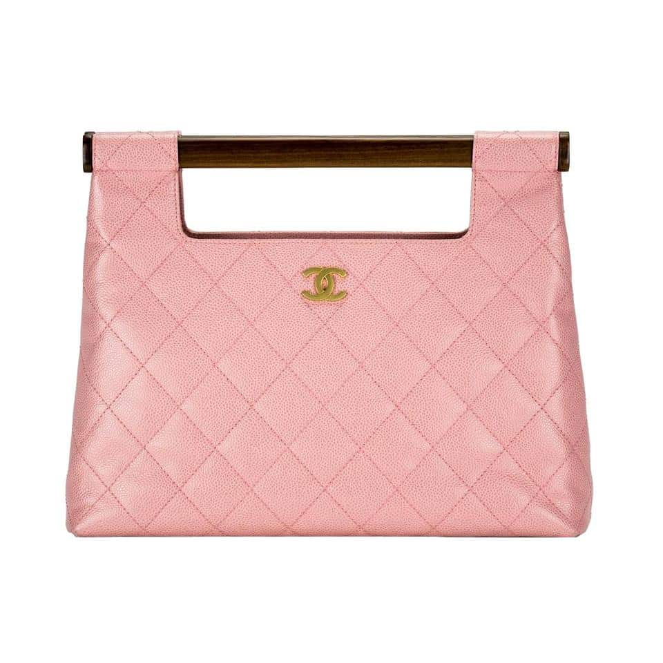 A pink quilted-leather Chanel handbag with wooden handles, offered by House of Carver