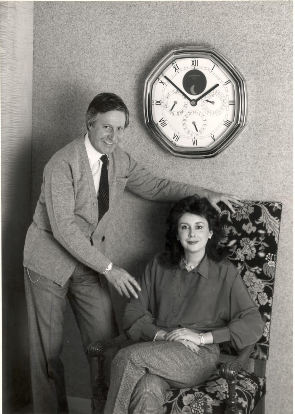 Watchmaker Gérald Genta, with his wife and business partner, Evelyne, posing beneath a clock of his own design