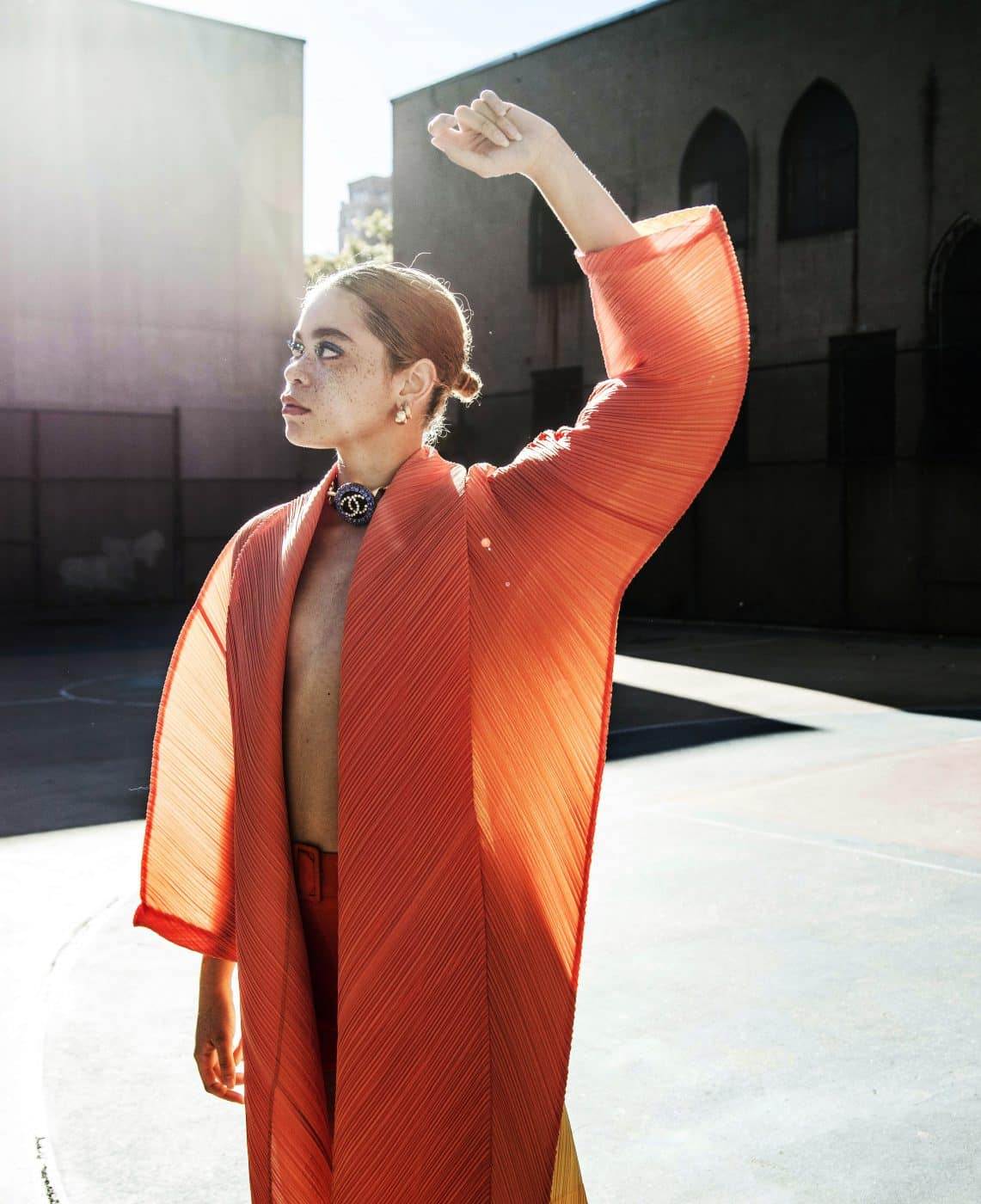 A model posing outdoors in an orange-and-yellow ISSEY MIYAKE COCOON JACKET, offered by Evolution