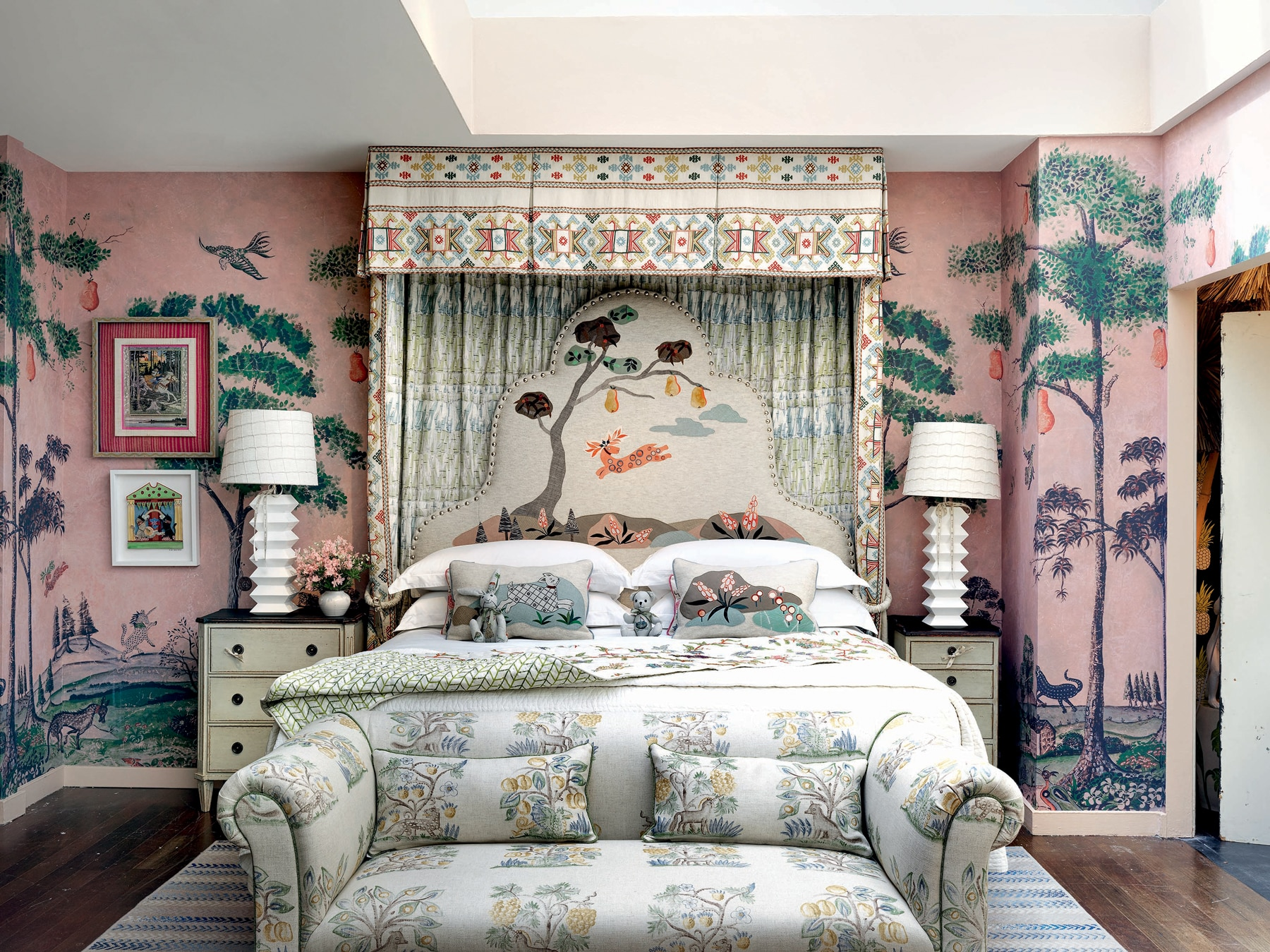 Bedroom with colorful nature wallpaper, matching white geometric lamps, and a nature printed couch