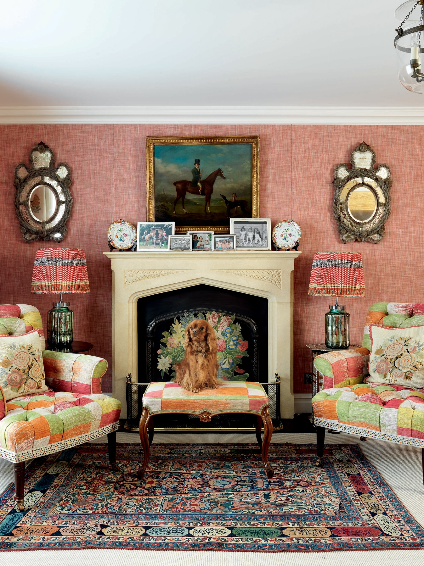 Living room space with matching multicolored armchairs and a dog sitting in front of a fireplace with a decorated mantle