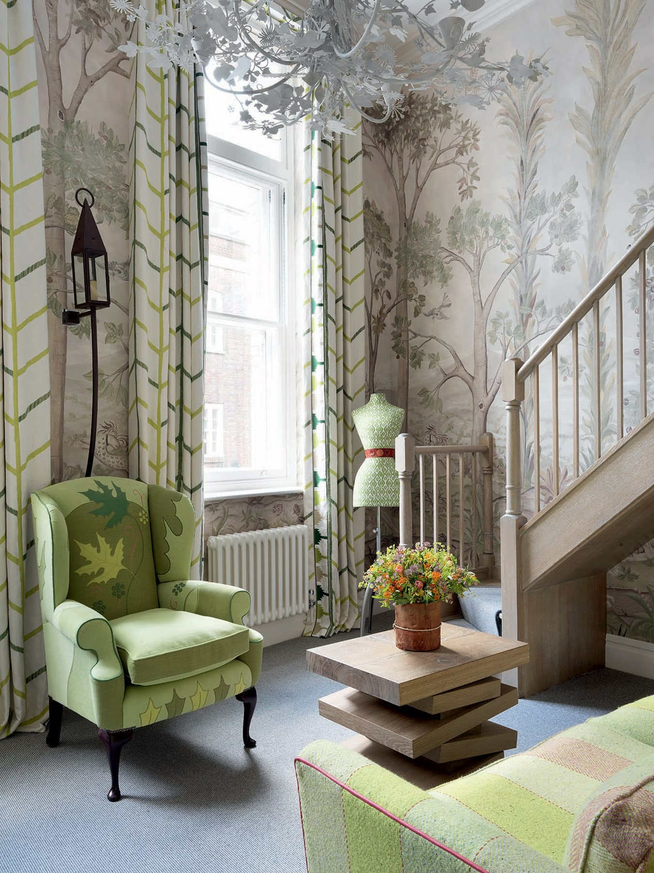 Sitting room interior space with tree patterned wallpaper, a green armchair, dress form, and couch