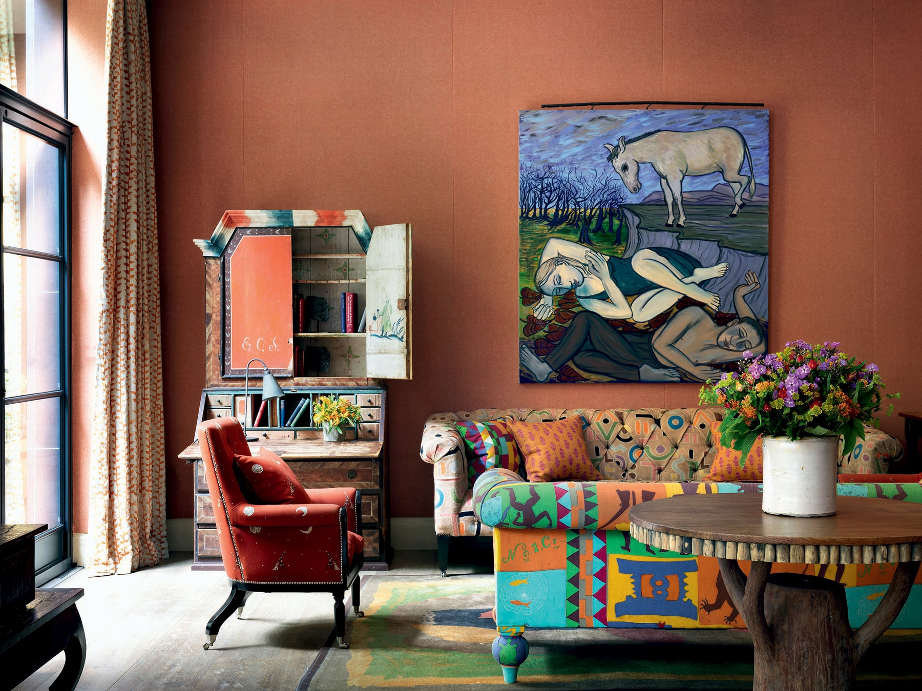 Living room space with wooden table, mismatched printed couches and armchair