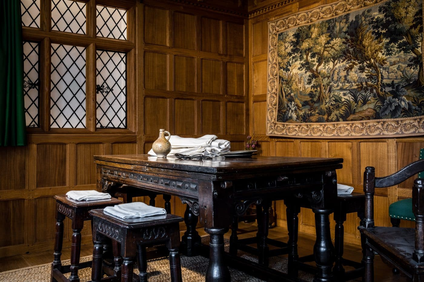 A display inside the Museum of the Home featuring a 1630 table and tapestry