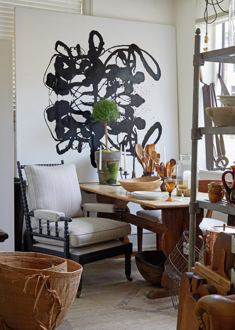 The early-20th-century French Zinc shelving unit and an 18th-century Swedish farmhouse table hold vessels like wooden serving bowls and glowing French copper pots