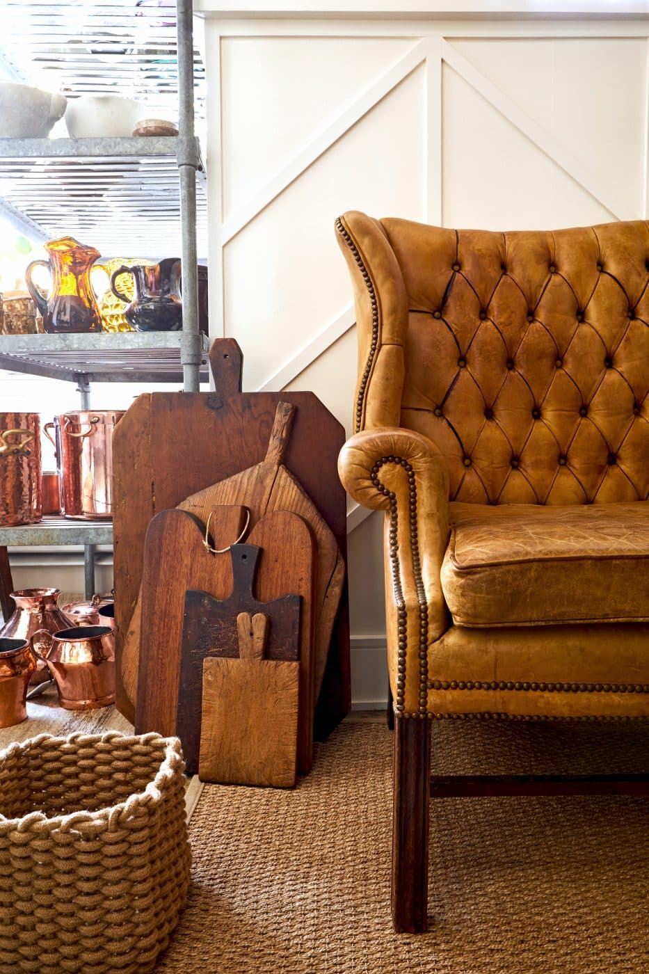 At Retzer's previous, Lincoln Park shop, an early-20th-century tufted leather settee and a collection of antique breadboards and cutting boards