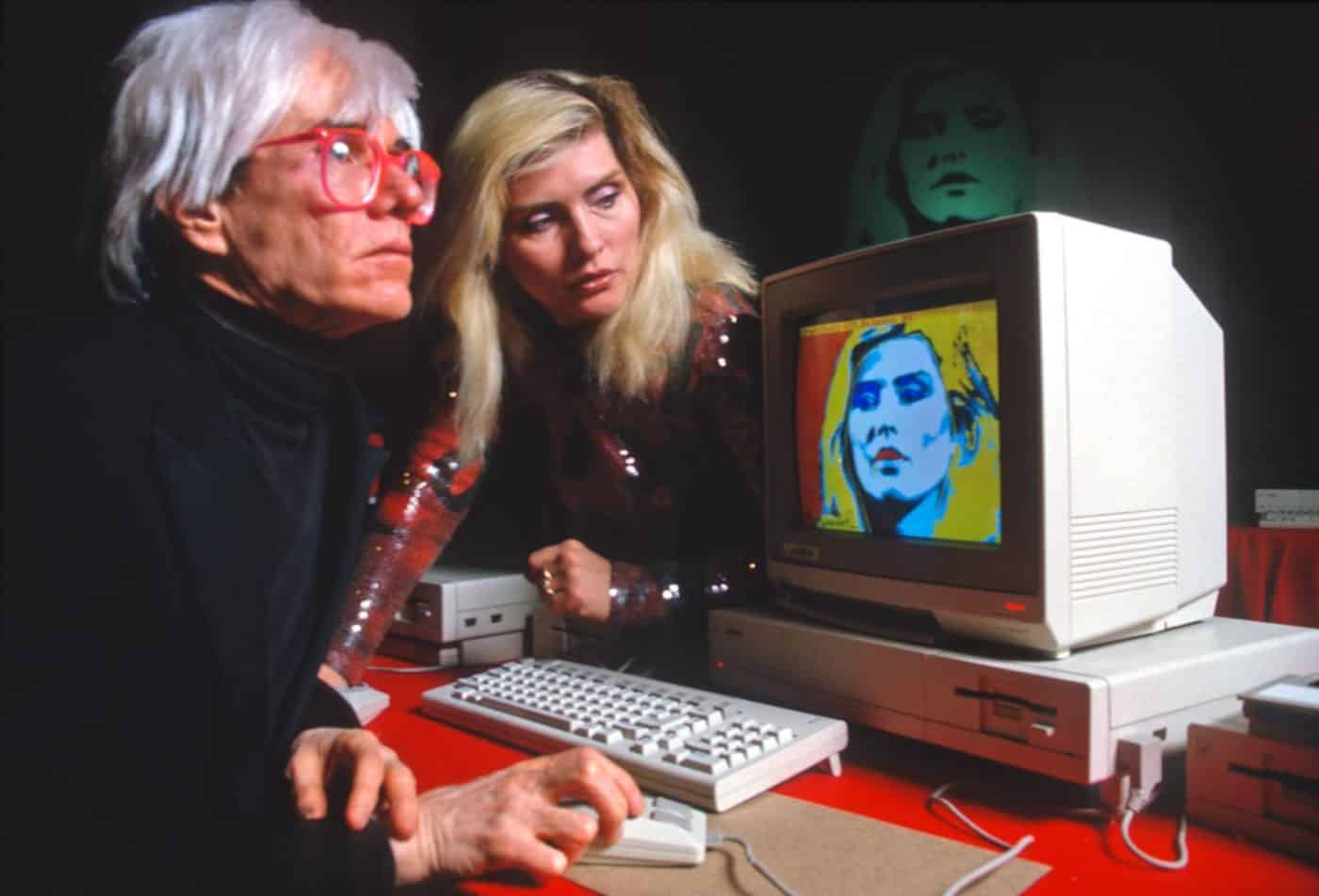 Andy Warhol with Blondie's Debbie Harry creating art on a mid-1980s Commodore personal computer