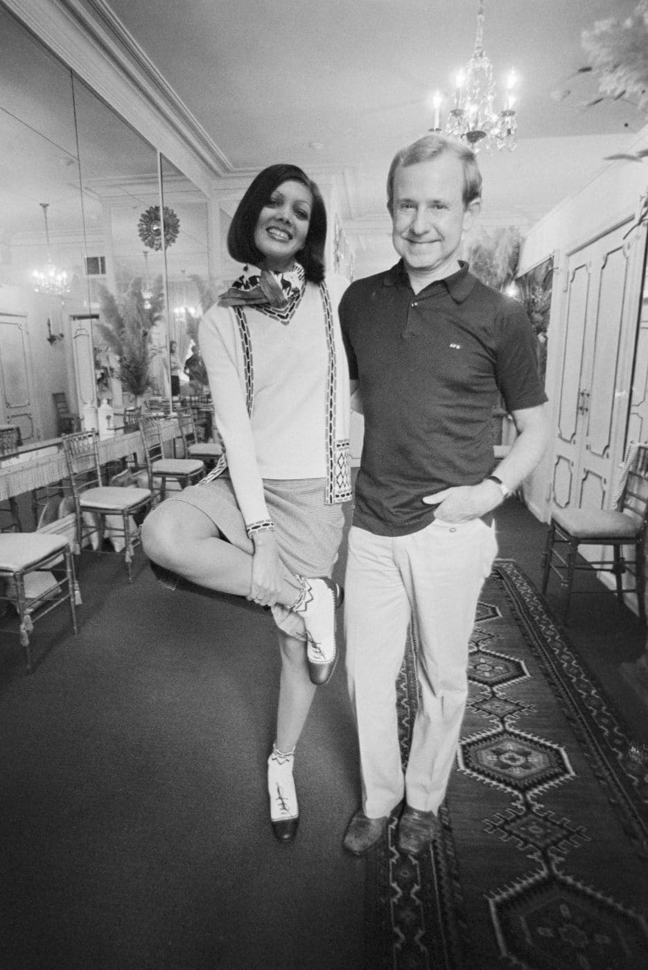 designer Adolfo, shown here with a model wearing one of his ensembles in 1979