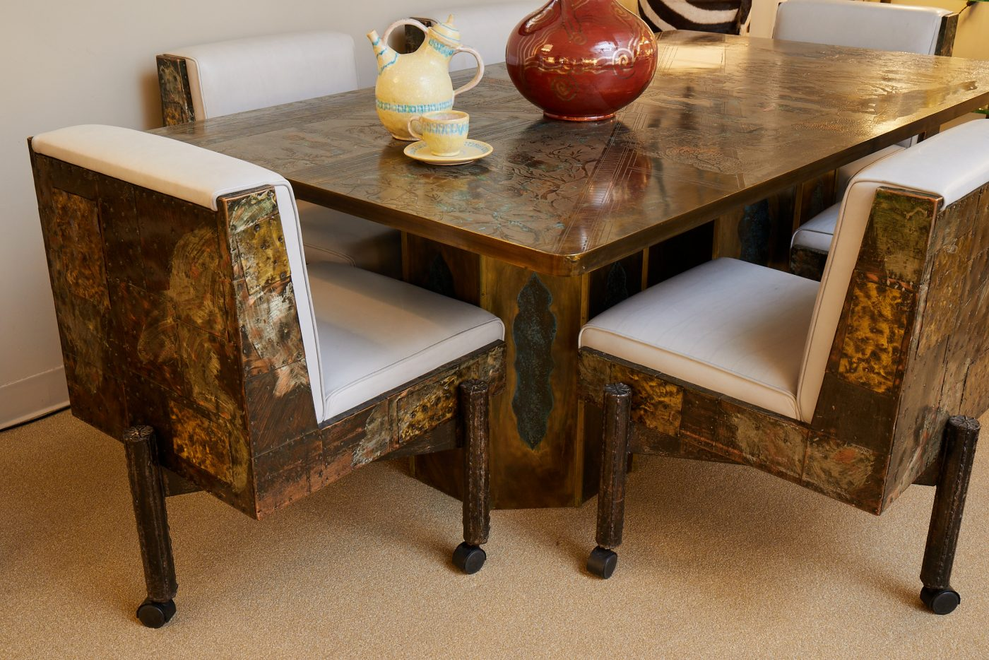 Pieces from a Guido Gambone ceramic on top of a Philip and Kelvin LaVerne dining table and Paul Evans dining chairs