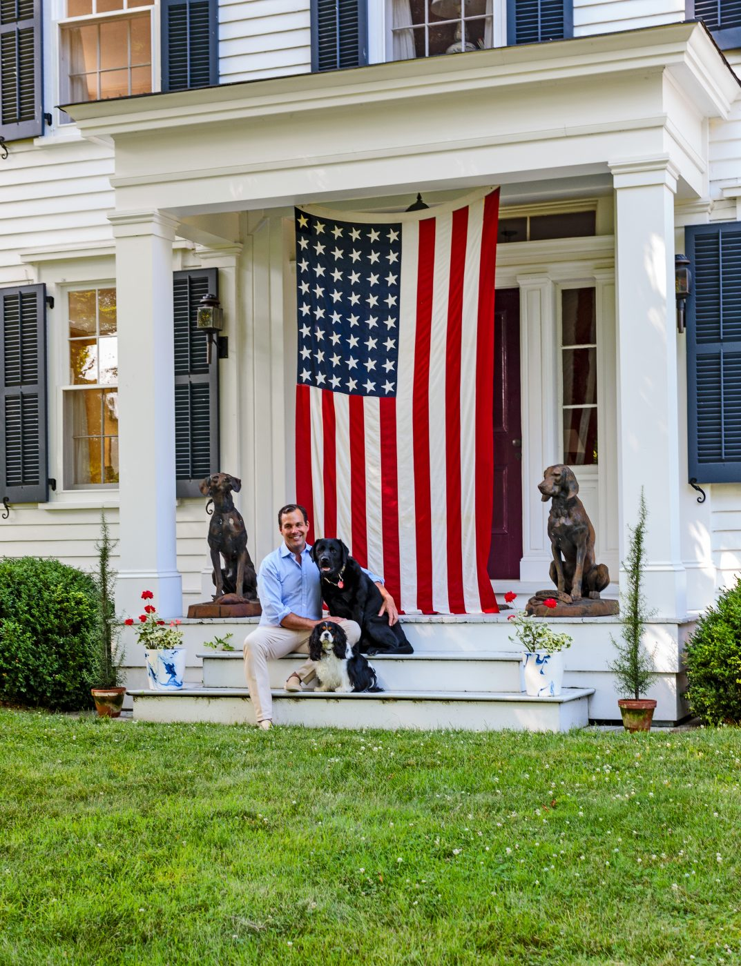 Christopher Spitzmiller with his dogs in front of his Hudson Valley, NY, farmhouse on Clove Brook Farm